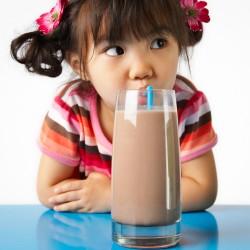 Girl Enjoying Chocolate Milk --- Image by © Royalty-Free/Corbis